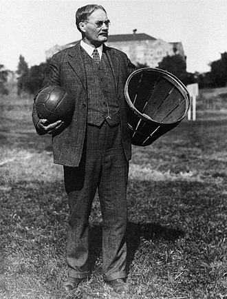 Basketball - Dr. James Naismith, the inventor of the game, stands with the original equipment for the game, a peach basket and a ball.