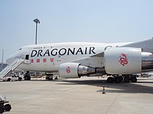 An aircraft in white colour, with the name Dragonair Cargo and Dragonair's Chinese name on its fuselage, parked on the tarmac.
