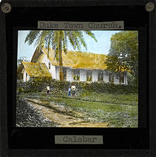 Image of the Duketown Church, Calabar (located within later day Nigeria). Three people stand in front of the white-sided church with a thatched roof. Duketown lies on the Calabar river 50 miles from the coast.