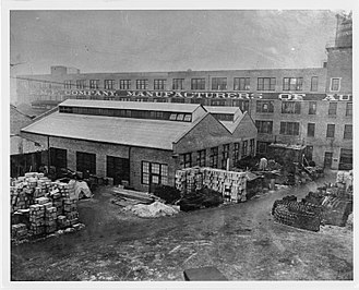 E-M-F Company - 8x10 black and white, sepia-toned photograph of the E.M.F. Company factory exterior with supply yard