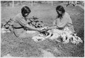 Elderly woman teaching her granddaughter the art of beadwork. - NARA - 285652.tif
