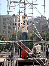 color image of the Phoenix 2 capsule held upright by scaffolds in a central square on display in Santiago, Chile
