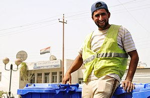 Waste collector - A smiling city worker prepares to unload new trash containers from a truck and distribute them to citizens of Basra, Iraq, July 1, 2009