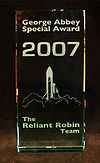 "A 2007 George Abbey Award, stating in white text ""George Abbey Special Award, 2007. The Reliant Robin Team."" Depicted is a drawing of a rocket launching with a Reliant Robin attached to it."