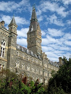 A large Gothic style stone building dominated by a tall clocktower.