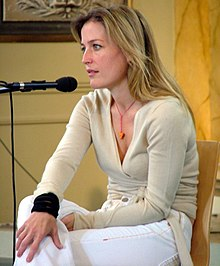 A blonde woman seated in front of a microphone