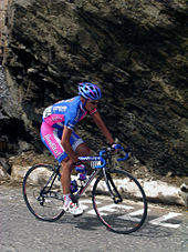 A cyclist wearing a blue and pink uniform while riding a bike.