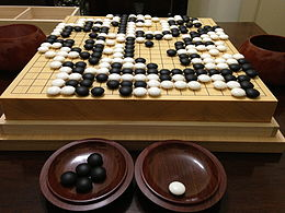 A wooden board with white and black stones