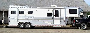 "Horse trailer - A ""gooseneck"" style horse trailer that also has living quarters in the front for people to use. It is attached to the bed of a pickup truck with a trailer ball coupling."