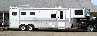 """Horse trailer - A """"gooseneck"""" style horse trailer that also has living quarters in the front for people to use. It is attached to the bed of a pickup truck with a trailer ball coupling."""