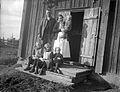 Gruppbild av en familj på trappan till sitt hus. Tre barn sitter, mannen och kvinnan står - Nordiska Museet - NMA.0057483.jpg