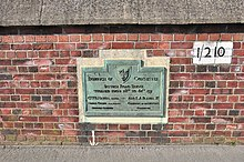 Green plaque mounted on a brick wall