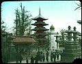 Japanese people (including some men in western dress) strolling through paved grounds among large stone lanterns; temples and pagoda. (19762246160).jpg
