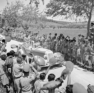 8th Infantry Division (India) - King George VI is driven past cheering Indian troops on his way to a ceremony to invest Sepoy Kamal Ram with the Victoria Cross, Italy, 26 July 1944.