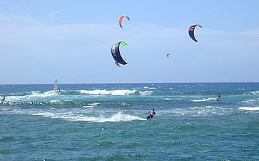 Kite surfing off in strong onshore winds off the north shore of O�ahu in Hawai�i. Note the wind-surfer catching the wave break.