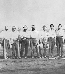 Seven members of the New York Knickerbockers baseball team standing on a field. They are wearing white shirts and dark pants.