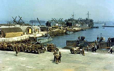 Degli LST prendono a bordo i camion, mentre le Jeep si dirigono verso i piccoli LCT in primo piano nel giugno 1944 durante i preparativi