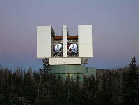 large binocular telescope with doors open, showing dual telescopes inside.