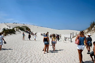 Łeba - Beachgoers on the white sand dunes of Łeba.