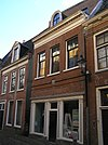 foto van Pand met geblokte kroonlijst waarboven halfronde dakkapel