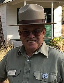 Les Joslin, in period Forest Service uniform with old forest guard badge, at the High Desert Museum's historic ranger station, 2018