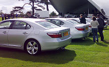 Five identical sedans lined up on a lawn. Two men and a woman are walking behind one sedan, carrying recording equipment.  The background has a stage, trailer, trees, and other persons