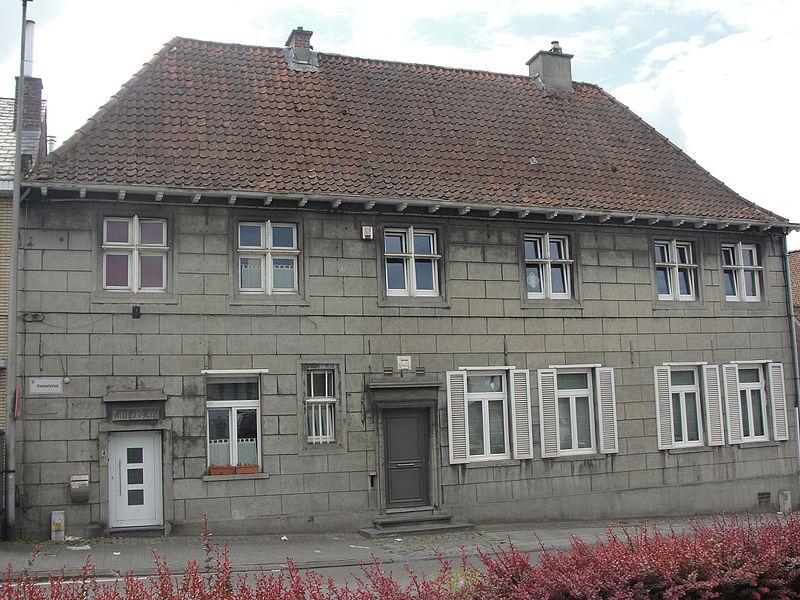 """Voormalig waaggebouw horende bij het verdwenen heerlijk kasteel van Liedekerke. In een cartouche boven de centrale deur staat de datering 1634. Constructie in vakwerkbouw, bekroond met een schilddak. Begin twintigste eeuw is de gevel gcementeerd en de ordonnantie in de linkertraveeën gewijzigd, door toevoeging van een deur, met datering """"anno 1902""""."""