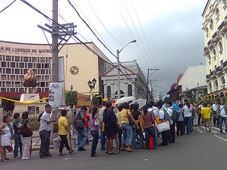 Death and funeral of Corazon Aquino - Queue for Aquino's wake at Manila Cathedral (its green cupola in background) in front of the Pamantasan ng Lungsod ng Maynila campus. The university offered mourners use of its facilities, such as its clinic and restrooms.
