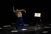 "Louise Lecavalier performing in Pite's work ""Lone Epic."" Beside the dancer is a music stand with sheet of paper displaying ""?""."