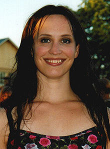 Picture of a 28-year-old woman with a black, open hair up to breast level and a wide smile