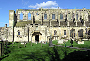 Malmesbury - The main entrance to Malmesbury Abbey (the South Porch) seen from the graveyard. This picture shows the full modern extent of the Abbey, to the right lie only ruins.