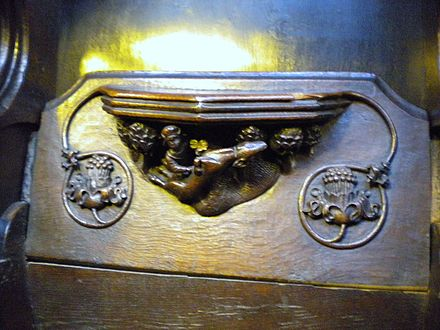 a misericord carving, depicting a hunter gutting a stag Manchester Cathedral 052.JPG