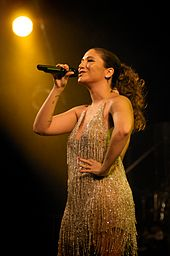 A woman in a beaded dress holding a microphone.