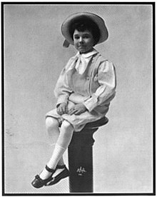 A black-and-white photographed of a neatly-dressed young boy in a hat, sitting on a pedestal