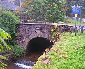 A brown and gray stone arch bridge just above a small cascade in a narrow creek with grass on one side and trees on the other. At the right is a blue-and-gold historical marker