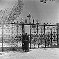 Monnik, vermoedelijk een franciscaan, in habijt bij het hek voor de kerk van de , Bestanddeelnr 255-0441.jpg