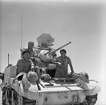 Three soldiers sitting on a tank