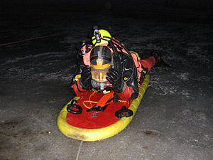 A diver wearing a dry suit skidding on the ice surface, on a special platform, at night.