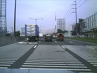 Rumble strip -  The North Luzon Expressway's raised plastic transverse rumble strips approaching Balintawak Toll Barrier, Philippines