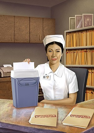Medical privacy - A nurse shredding papers in order to be compliant with the physical safeguard section of the Health Insurance Portability and Accountability Act (HIPAA).
