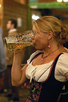 a beerdrinking woman at oktoberfest in munich wearing a