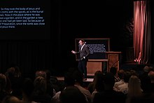 "Mark Driscoll preaching at Mars Hill Church, set against a large projected image that reads ""Ten Commandments: set free to live free"""