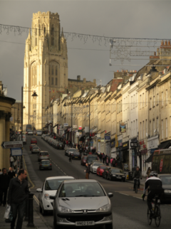 Park Street, Bristol. A steeply-sloped busy shopping street with light stone-coloured Georgian buildings on both sides. At the top is the ornate and dominant tower of the Wills Memorial Building.