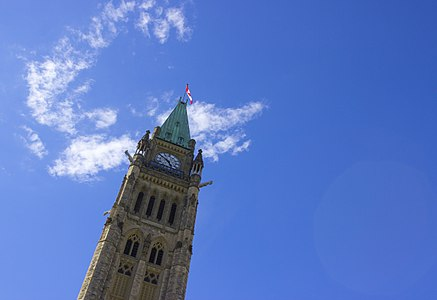 Peace Tower of the Parliament of Canada in Ottawa, Canada at an angle, under clouds.