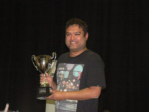 Paul Sinha holding the Fighting Talk Champion of Champions Trophy