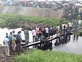 Pedestrians in Lagos trying to cross a makeshift bridge.jpg