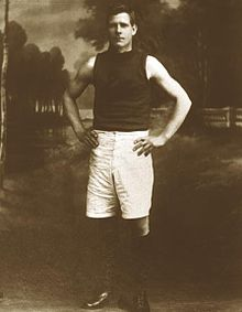 Sepia colours posed photograph of young man standing with hands on hips, wearing a dark sleeveless jumper, long white shorts and black boots