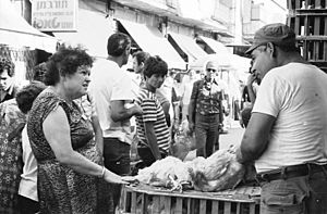 Kapparot - A vendor at Mahane Yehuda Market in Jerusalem sells roosters for kapparot before Yom Kippur.