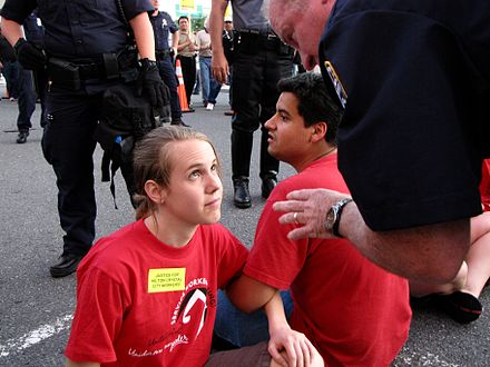 A police officer speaks with a demonstrator at a union picket, explaining that she will be arrested if she does not leave the street. The demonstrator was arrested moments later. Police officer speaking to demonstrator during civil disobedience action.jpg