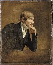 An oil on canvas in brown tones of a white man with short brown hair. He is sitting side-on, facing to the right of the picture, with his chin on his left hand, he wears a frock coat and shirt with a wide neck tie. He has a faint smile.